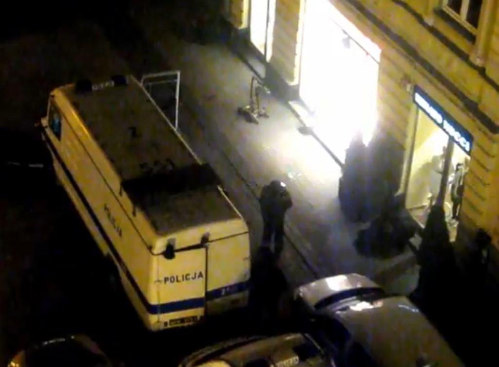 Kadr z filmu wrzuconego na Youtube przez użytkownika netpozytywny.pl. Pod witryną sklepu widać policyjnego robota do neutralizowania ładunków wybuchowych