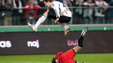 Rafał Wolski z Legii przeskakuje nad Sebastianem Przyrowskim z Polonii. Derby Warszawy, Legia - Polonia, 16 marca 2012