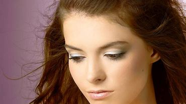 Makijaż w stylu Chanel - cera rozjaśniona jest naturalnym, świetlistym podkładem. Makijaż jest utrzymany w tonacjach bieli, złota i czerni. Mleczny błyszczyk ze srebrnymi drobinkami nałożony jest bez konturówki. Ciemna, czarna kreska poprowadzona jest wzdłóż linii rzęs.