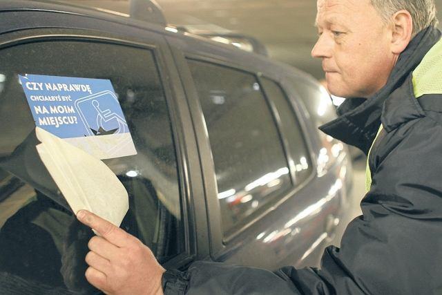 Ochroniarz Jacek Łażewski z Reduty przykleja naklejkę na szybie samochodu zaparkowanego na kopercie