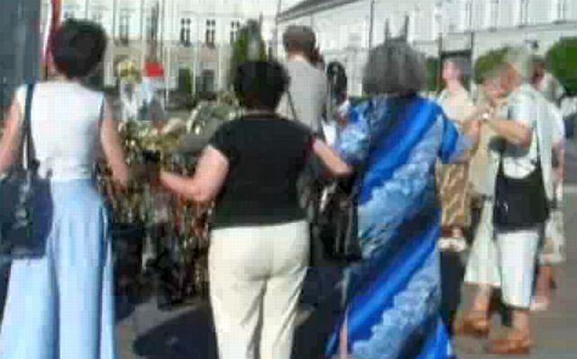 Starsze panie broniące krzyża przed Pałacem Prezydenckim tańczą