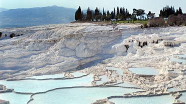 Azja Pamukkale, Turcja. Nieduża miejscowość w pobliżu Denizli w Turcji. Ciekawostką geograficzną, która rozsławiła Pamukkale na świecie są baseny termalne i białe osady wapna na ścianach wzgórza Cokelez. Woda spływająca zboczem góry gromadzi się tu w licznych nieckach, które tworzą charakterystyczne tarasy.