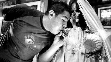 Wyznawca Świętej Rodziny okadza dymem z cygara jej figurkę. Tepito, dzielnica Meksyku