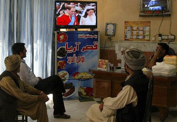 Afghans gather around a television in a restaurant in Herat province April 29, 2011 to watch the live telecast of Britain's royal wedding of Prince William and Kate Middleton. REUTERS/Mohammad Shoiab (AFGHANISTAN - Tags: SOCIETY ROYALS)