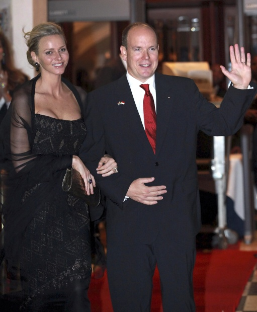 Prince Albert II of Monaco, right, with Princess Charlene, left, waves as they pose for the photographers outside a hotel in Durban, South Africa, Thursday July 7,  2011. Monaco's new princess took a break from her South African wedding reception Thursday to share a kiss with her prince for the cameras. Princess Charlene, who was raised in South Africa, and Prince Albert II appeared briefly before journalists who had been entertained by a Zulu song-and-dance troupe as they watched VIPs, including International Olympic Committee President Jacques Rogge, walk down a red carpet into the luxury Oyster Box restaurant and hotel.(AP Photo/Rajesh Jantilal)