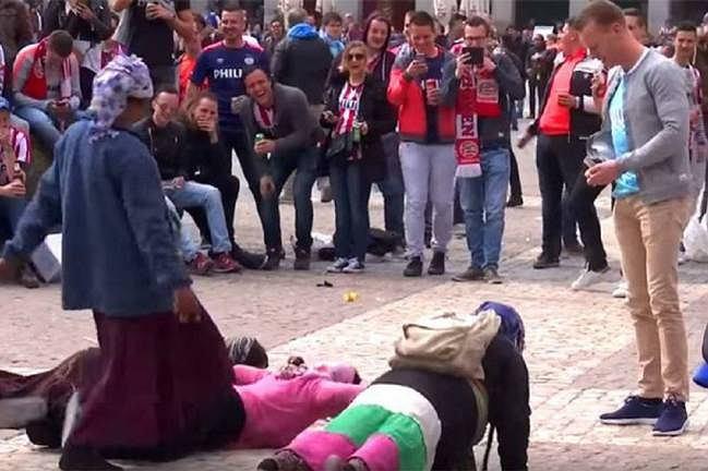 Kibice PSV rzucający monetami w żebraków