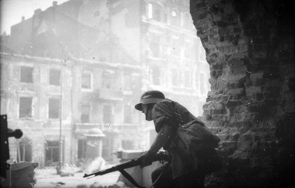 Krakowskie Przedmieście, żołnierz obserwujący przedpole na tle zniszczonej zabudowy. Od lewej kamienice nr: 10, 8 i 6.