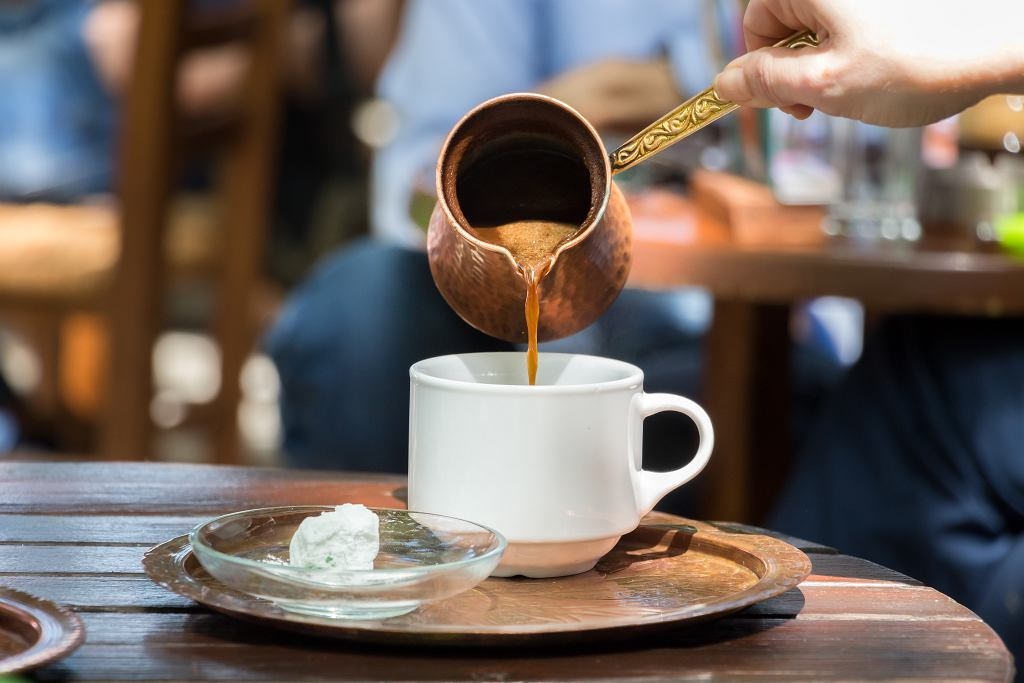 4Woman,Hand,Pouring,Greek,Coffee,From,A,Copper,Pot,On