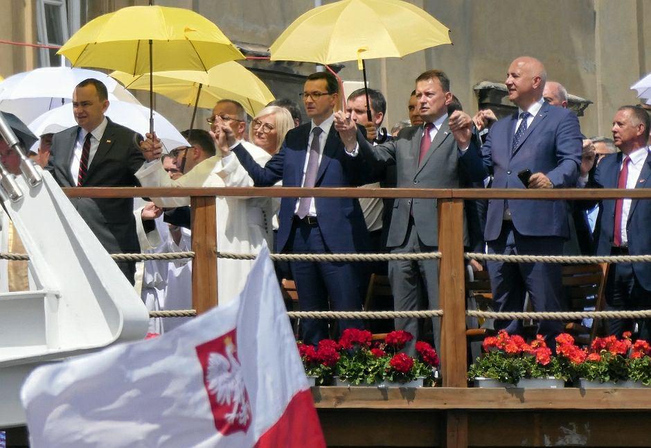 Premier Mateusz Morawiecki, szef MON Mariusz Błaszczak, szef MSWiA Joachim Brudziński, w tle rzeczniczka rządu Joanna Kopcińska