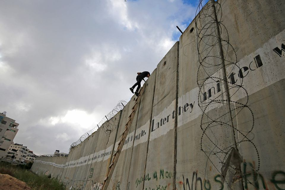Młody Palestyńczyk wspina się na mur oddzielający Izrael od Autonomii Palestyńskiej, 2019 r.
