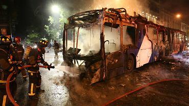 Chile. Strażacy dogaszają podpalony przez protestujących autobus.