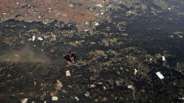 Chłopiec szuka materiałów do wtórnego przetworzenia, pływając w potwornie zanieczyszczonej rzeki Kuakhai w Indiach