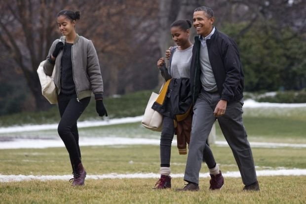 President Barack Obama, right, hugs his daughter Sasha as they and Malia, left, return to the White House from their fifteen-day family vacation in Hawaii, on the South Lawn of the White House in Washington, Sunday, Jan. 5, 2014. First lady Michelle Obama stayed behind in Hawaii as a birthday present from her husband. (AP Photo/Jacquelyn Martin)
