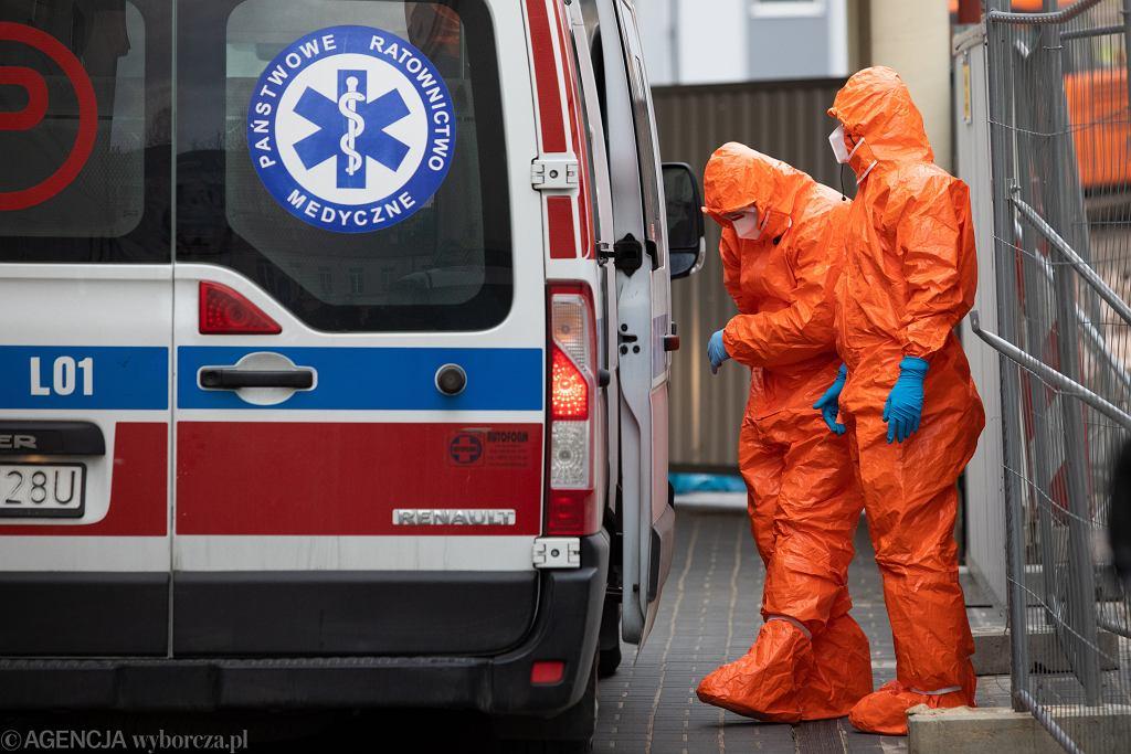 Epidemia koronawirusa - karetka i ratownicy ubrani w stroje ochronne (zdjęcie ilustracyjne)