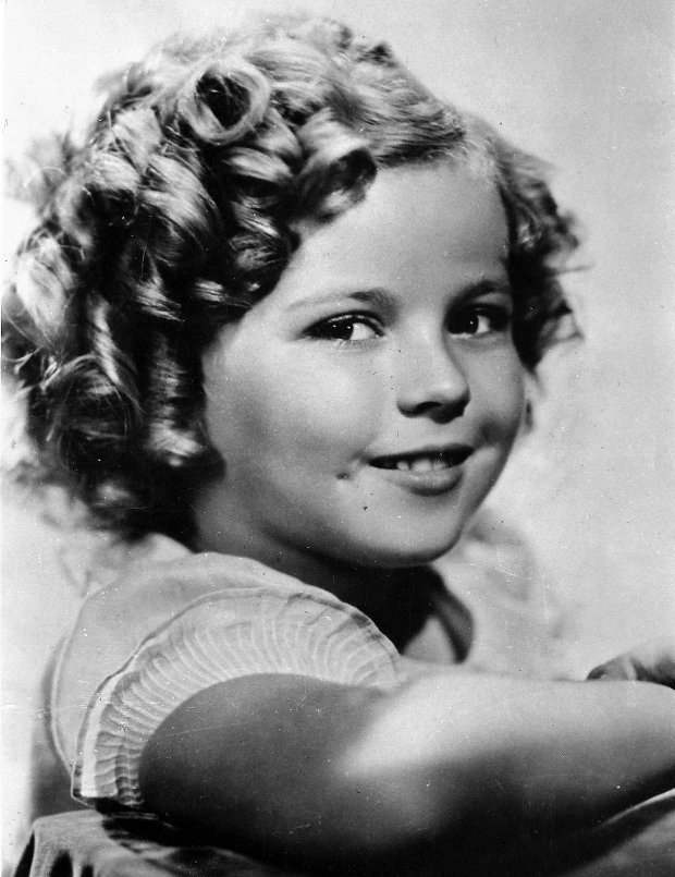 FILE - In this Nov. 1936 file photo, 8-year-old U.S. American child movie star Shirley Temple is portrayed in Hollywood, Ca., USA. Shirley Temple, the curly-haired child star who put smiles on the faces of Depression-era moviegoers, has died. She was 85. Publicist Cheryl Kagan says Temple, known in private life as Shirley Temple Black, died surrounded by family at her home near San Francisco. (AP Photo/File) SLOWA KLUCZOWE: smiling
