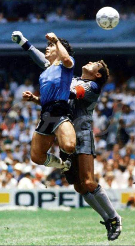 Diego Maradona przerzuca piłkę ręką obok wyciągniętej ręki Petera Shiltona