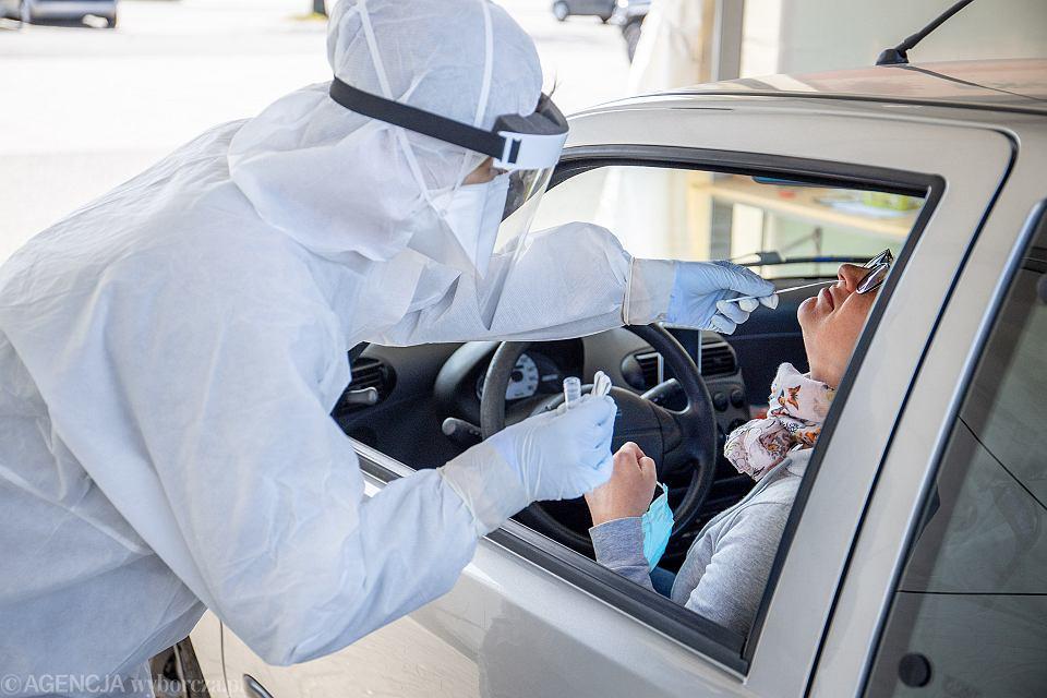Pracownik mobilnego punktu diagnostycznego wykonuje test na koronawirusa