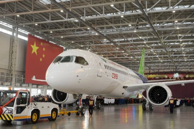 The first C919 passenger jet made by the Commercial Aircraft Corp of China (Comac) is pulled out during a news conference next to a Chinese national flag at the companys factory in Shanghai, November 2, 2015. Comac rolled out Chinas first homemade 158-seated C919 narrow body jet, which is meant to rival similar models from Airbus Group and Boeing Co. State television also showed footage of the aircraft rolling off the assembly line in Comacs Shanghai factory. In a statement, the company said it had already received 517 orders for the aircraft mainly from domestic firms. REUTERS/China Daily CHINA OUT. NO COMMERCIAL OR EDITORIAL SALES IN CHINA