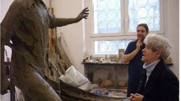 Krystyna Cieślik ogląda rzeźbę w pracowni artysty