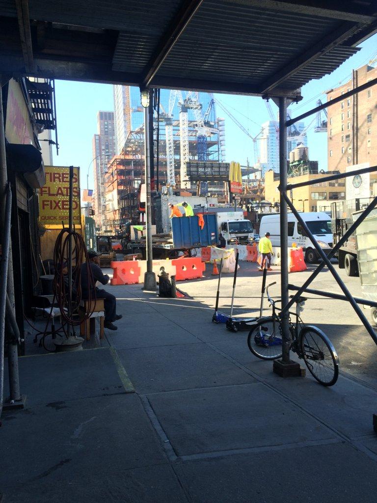 Zakład wulkanizacji opon na tle budowy nowego biurowca. Manhattan, Nowy Jork.