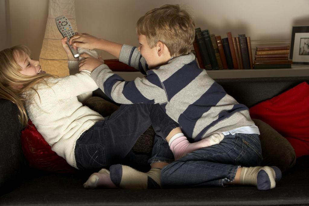 Dzieci kłócą się o pilot do telewizora.