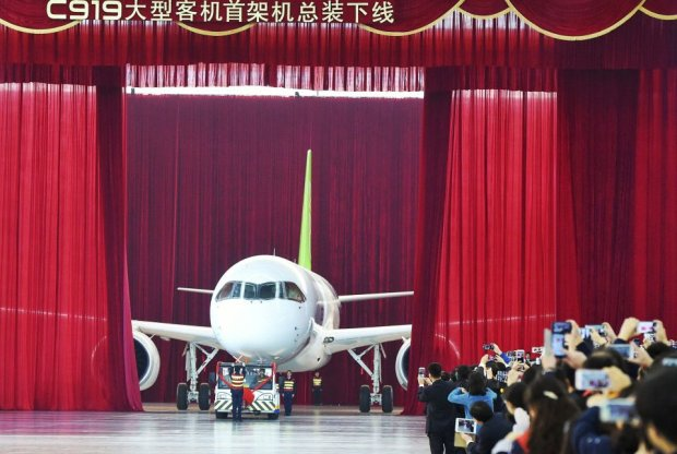 People take pictures and videos as the first C919 passenger jet made by the Commercial Aircraft Corp of China (Comac) is pulled out during a news conference at the companys factory in Shanghai, November 2, 2015. Comac rolled out Chinas first homemade 158-seated C919 narrow body jet, which is meant to rival similar models from Airbus Group and Boeing Co. State television also showed footage of the aircraft rolling off the assembly line in Comacs Shanghai factory. In a statement, the company said it had already received 517 orders for the aircraft mainly from domestic firms. REUTERS/Stringer CHINA OUT. NO COMMERCIAL OR EDITORIAL SALES IN CHINA