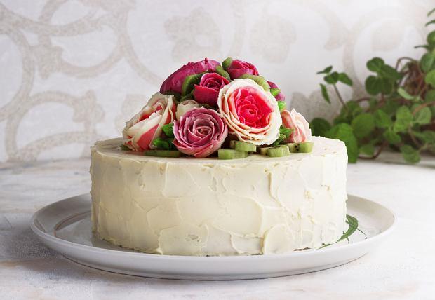 Tort na komunię dla dziewczynki można pięknie ozdobić świeżymi kwiatami, na przykład różami lub jaskrami