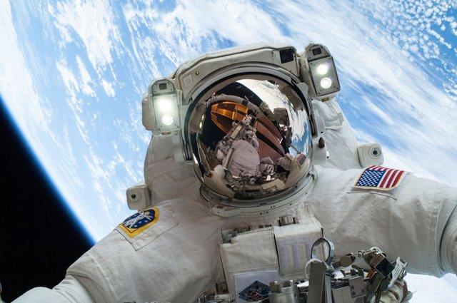 Astronauta Mike Hopkins robi sobie fotkę z ręki podczas spaceru w przestrzeni kosmicznej. W wizjerze hełmu odbija się Rick Matracchio.