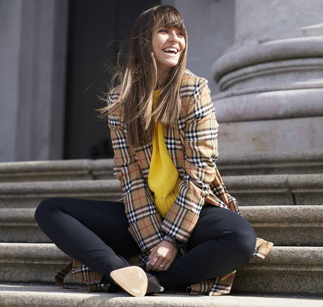 Anna Lewandowska w płaszczu Burberry i żółtym swetrze