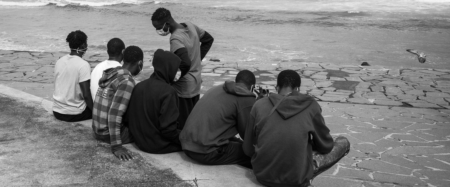 Grupa nastolatków z ogarniętego wojną Mali przygląda się surferom łapiącym fale, Puerto de la Cruz, Teneryfa (fot. Karol Grygoruk / RATS Agency)