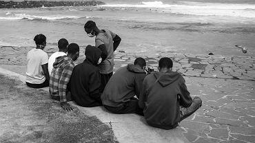 Un grup de adolescenți din Mali, devastat de război, care privesc surferii cum prind valurile, Puerto de la Cruz, Tenerife