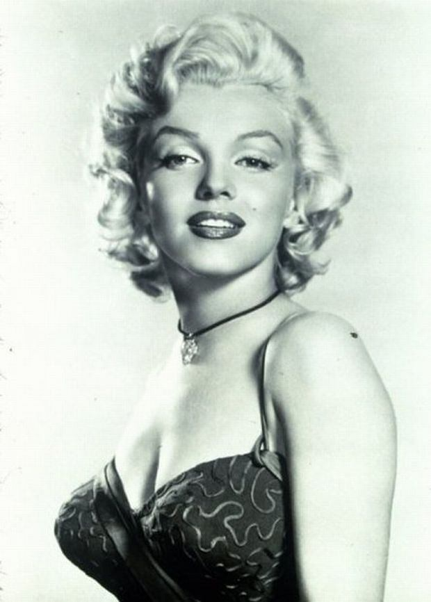 1953, Film Title: GENTLEMEN PREFER BLONDES, Director: HOWARD HAWKS, Studio: FOX, Pictured: 1953, PORTRAIT, Halterneck, Bombshell, Sexy, Cleavage, Blonde, Bottle Blonde, Heavy Eyelids, Looking Over Shoulder, Sultry, Vixen, Red Lips, Studio. MARYLIN MONROE