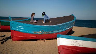 Pandemia koronwirusa. Dzieci w maskach bawią się na plaży pod Barceloną, 28 kwietnia 2020 r.