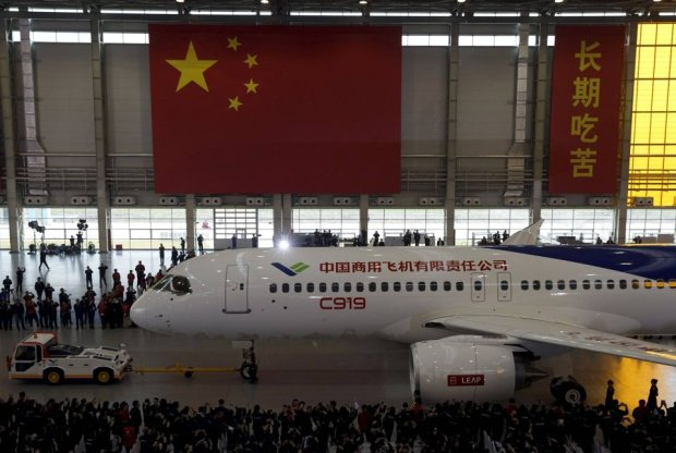 The first C919 passenger jet made by the Commercial Aircraft Corp of China (Comac) is pulled out during a news conference next to a Chinese national flag at the companys factory in Shanghai, November 2, 2015. Comac rolled out Chinas first homemade 158-seated C919 narrow body jet, which is meant to rival similar models from Airbus Group and Boeing Co. State television also showed footage of the aircraft rolling off the assembly line in Comacs Shanghai factory. In a statement, the company said it had already received 517 orders for the aircraft mainly from domestic firms. REUTERS/Stringer CHINA OUT. NO COMMERCIAL OR EDITORIAL SALES IN CHINA