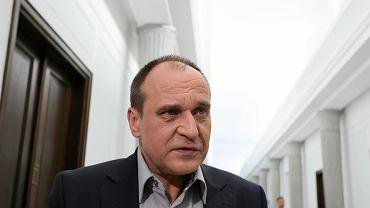 Paweł Kukiz udzielający wypowiedzi na sejmowym korytarzu.