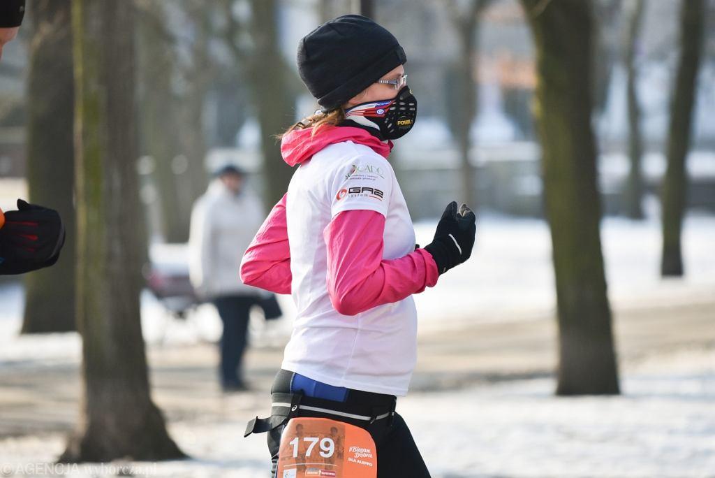 Bieg #BiegamDobrze dla Aleppo' w Warszawie, biegaczka w masce przeciwsmogowej (fot. Franciszek Mazur/AG)