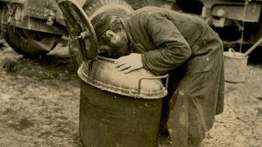Żyd zmuszony do czyszczenia niemieckiej kuchni polowej. Zdjęcie wykonane przez żołnierza Wehrmachtu. Miejsce nierozpoznane, 1939 r