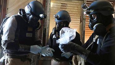 Eksperci ONZ w maskach przeciwgazowych trzymają plastikową torbę z próbką do badania na obecność bojowych środków trujących
