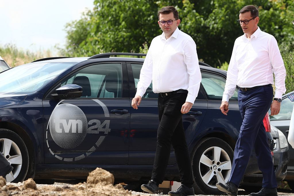 Premier na tle samochodu TVN24