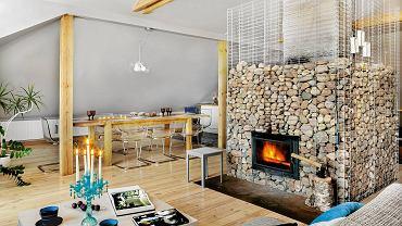 Kamienie w okalającym kominek gabionie to nie tylko efektowna dekoracja. Gdy płonie ogień, szybko się nagrzewają, a potem oddają ciepło jeszcze długo po wygaśnięciu paleniska