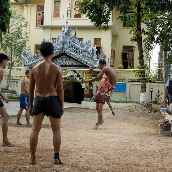 Podwórko w Birmie - mężczyźni grają w chinlone, popularną w Azji siatkonogę