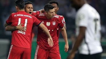 Bayern's Robert Lewandowski, right, celebrates with team mates James, Thiago, background left, and David Alaba, background right, after scoring his side's opening goal during the German soccer cup final match between FC Bayern Munich and Eintracht Frankfurt in Berlin, Germany, Saturday, May 19, 2018. (AP Photo/Michael Sohn)