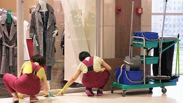 Sprzątaczki czyszczące korytarz w centrum handlowym.