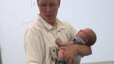 Prof. Ryan prowadzi zajęcia trzymając na rękach 3-tygodniowego Isaiah, synka swojej studentki