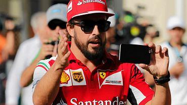 'Czekajcie, trochę w lewo, zaraz, który profil mam lepszy?' - przed startem GP Abu Dhabi Fernando Alonso usiłuje zrobić zdjęcie. Sobie? A może chce odwrócić role i, dla odmiany, sfotografować fotoreporterów?