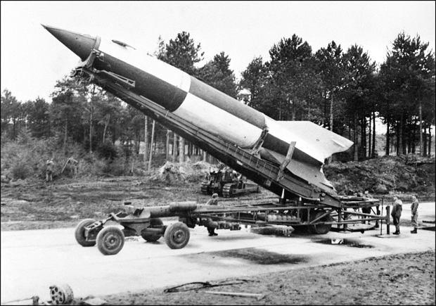 Rakieta V-2 w trakcie stawiania jej pionowo na stole startowym.  Zdjęcie wykonano prawdopodobnie w Peenemünde. Procedura startowa odbywała się w trakcie rekultywacji terenu przez spychacz i wycinkę drzew prowadzoną w głębi kadru