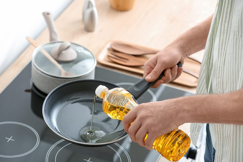 2Man,Pouring,Sunflower,Oil,On,Frying,Pan,In,Kitchen