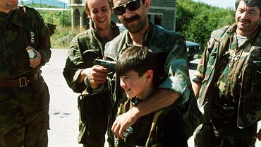 Serbski dowództwa przykłada pistolet do głowy swojego syna, żartując z kolegami podczas oczekiwania na wymianę więźniów. Okolice Sarajewa, 1992 r.