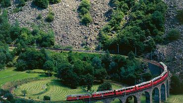 Koleje Retyckie Albula/Bernina. Czerwone pociągi mkną po zakręconym wiadukcie Brusio.