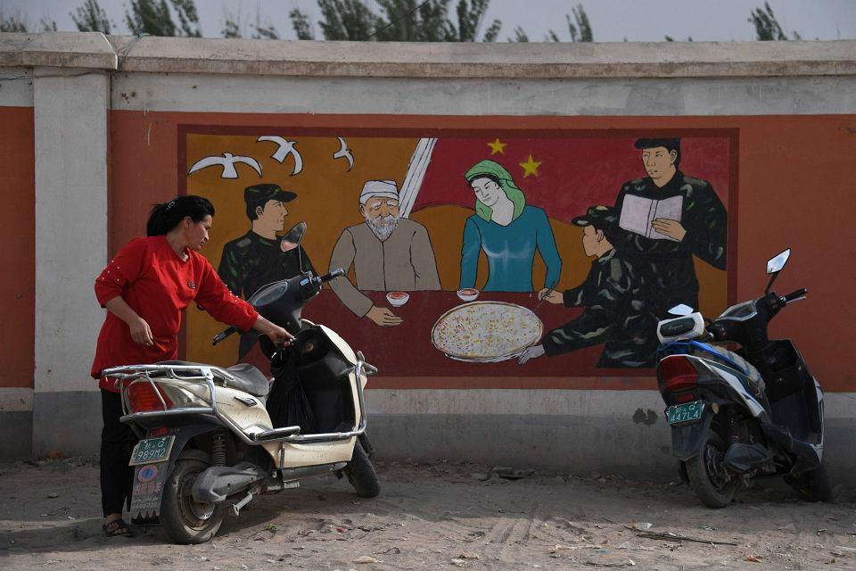 Ujgurka parkuje motocykl przed szpitalem wojskowym w mieście Kaszgar; propagandowe malowidło na murze przedstawia żołnierzy odwiedzających ujgurską rodzinę. Autonomiczny region Sinciang, 2 czerwca 2019 r.